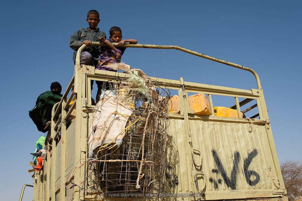 Children atop a truck loaded with Malian refugees and their meagre belongings as it stands parked in the heat on the edge of the Mbera refugee camp in Mauritania while it waits for the rest of the convoy to catch up, on 6 March 2013. According to local NGO, ALPD, 825 refugees arrived in this convoy, packed into three trucks and an assortment of four wheel drive pick-ups.