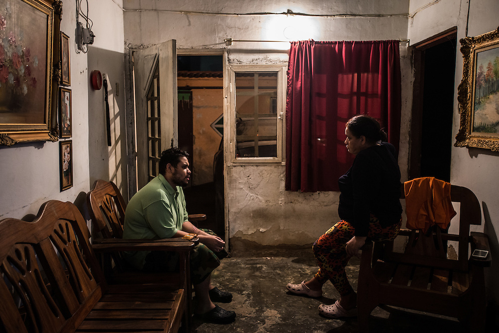MARACAY, VENEZUELA - JULY 4, 2016: Evelin RodrÍguez (right) listens as her schizophrenic son, Accel Simeone (left), who did not have all of the medicines that he needs, explains to her that the room is full of angry hip-hop artists like Nicki Minaj and Ñengo Flow, a Puerto Rican singer, that are sitting in every seat in the living room, insulting him, and demanding that he stay completely still - threatening to throw a bomb at him if he moves even the slightest bit. He asked politely that no one sits on the furniture until the musicians had left, in fear of making them upset by sitting on them. Evelin calmly explained that they were alone in the room, and that the voices are not real and cannot hurt him. The month before, Accel said the voice of Ñengo Flow, who torments Accel the most, demanded he kill his brother Gerardo. When he refused, he ordered him to cut off his arm, and so he attacked himself. He took an electric circular saw from the family's garage, switched it on and began slicing into his arm. Thankfully, his father found him and wrestled away the saw before he could do major damage to his arm.   PHOTO: Meridith Kohut for The New York Times