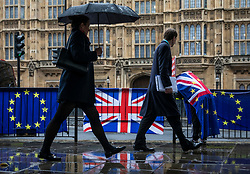 © Licensed to London News Pictures. 02/04/2019. London, UK. Pedestrians shelter beneath umbrellas as they pass anti-Brexit protesters opposite Parliament. Prime Minister Theresa May is chairing a Cabinet meeting to try and agree a path forward with ministers after MPs voted to reject all alternatives to the Withdrawal Agreement for a second time. Photo credit: Rob Pinney/LNP