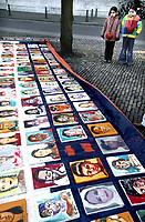 Nederland. Den haag, 19 februari 2004.<br />Kunstenaars hebben 300 schilderijen gemaakt van kinderen die onder de regeling van minister Verdonk uitgezet zullen worden. De portretten werden op een groot rood-wit-blauw doek opgehangen. Generaal pardon. Asielzoekers. Uitzettingsbeleid. Twee van de geportretteerden staan bij het kunstwerk.<br /><br />Foto Martijn Beekman<br />niet voor trouw,ad,parool en nrc