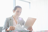 Young businesswoman using tablet PC while reading book in office