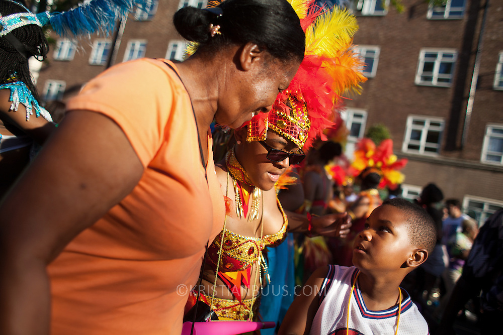 A young boy gets some attention from a couple of women dancing along in the road. The Notting Hill Carnival has been running since 1966 and is every year attended by up to a million people. The carnival is a mix of amazing dance parades and street parties with a distinct Caribbean feel.