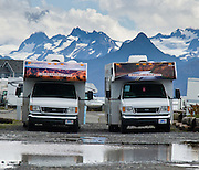 "CruiseAmerica RVs park beneath glaciated peaks in Homer, on the shore of Kachemak Bay, Kenai Peninsula, Alaska, USA. The town of Homer claims to be the ""halibut fishing capital of the world."" Village nicknames include ""Homer - a quaint little drinking village with a fishing problem"" [bumper sticker] and ""the end of the road."" Homer is the southernmost town on the contiguous Alaska highway system: the end of Sterling Highway, part of Alaska Route 1."