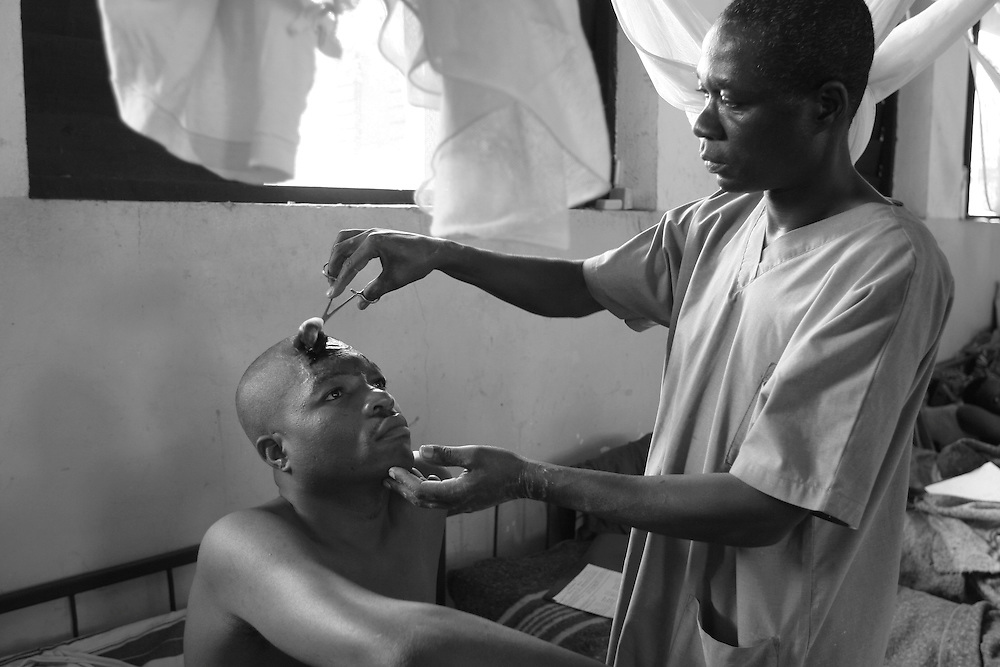 An MSF doctor treats a patient after he got injured by grenade on his forhead at CBL Center of Bujumbura ( Center for injured people). @ Martine Perret . 24 October 2005.
