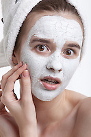 Portrait of shocked young woman with face mask peeling off against white background