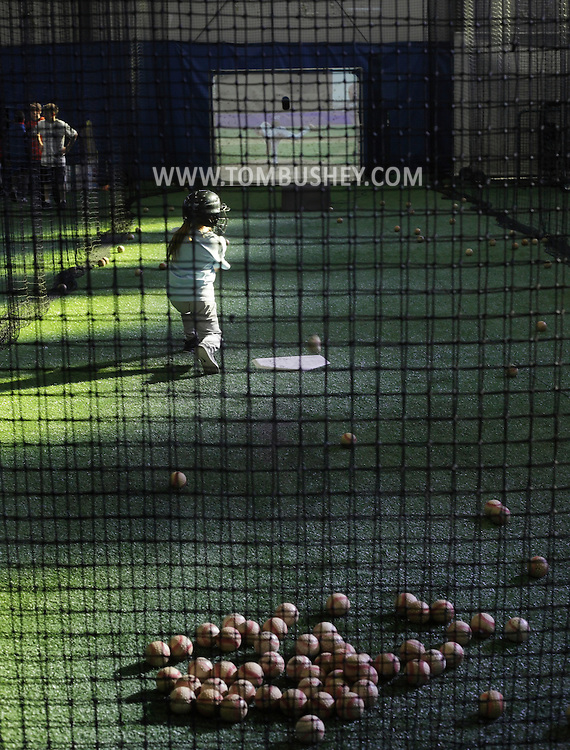 Chester, New York  - A girl takes a swing in a batting cage during the first anniversary open house celebration at The Rock Sports Park on Nov. 12, 2011.