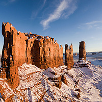 USA, Arizona, Monument Valley Navajo Tribal Park, Aerial panoramic view of setting winter sun lighting snow-covered sandstone mesas in Monument Valley
