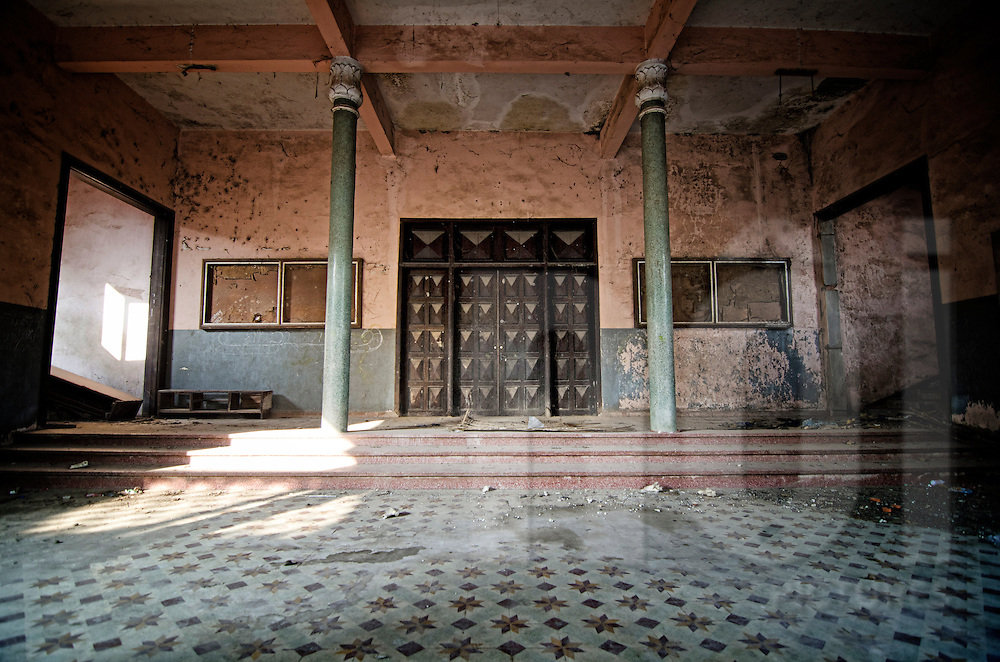 Abandoned Sengchaleun cinema, Savannakhet, Laos, Asia. Interiors are in complete decay and very messy. Old wooden doors entry are closed