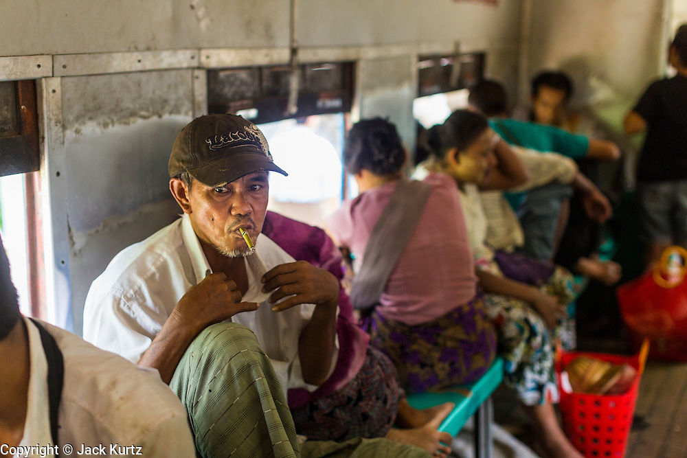 05 JUNE 2014 - YANGON, YANGON REGION, MYANMAR: A man smoke a cheroot on the Yangon Circular Train. The Yangon Circular Train is a commuter train that circles Yangon, Myanmar (Rangoon, Burma). The train is 45 kilometers long, makes 38 stops and takes about three hours to make a loop of the city.     PHOTO BY JACK KURTZ