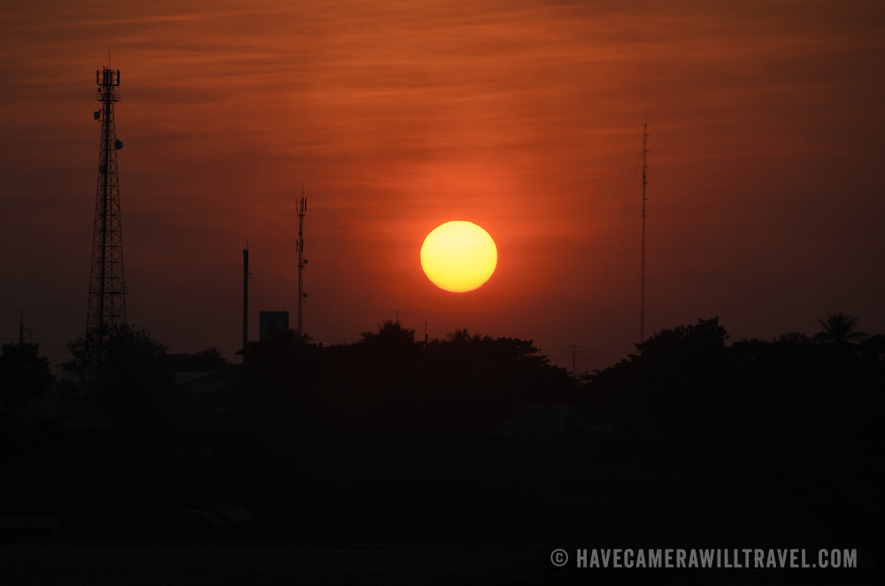 The setting sun creates a silhouette of the landscape across the Mekong River in Vientiane, Laos. Because the river marks the border between Laos and Thailand, the trees and communications towers that are silhouetted on the far bank are actually in Thailand.