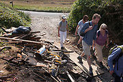 Countryside ramblers walk past a heap of dumped and burned fly-tipped rubbish on a footpath, on 27th August 2017, near Cobham, Kent, England.