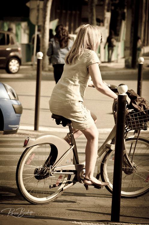 Woman riding a bicycle, Paris, France