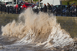 © Licensed to London News Pictures. Clevedon, North Somerset, UK; 03/03/2019; Storm Freya. Members of the public watch the waves at high tide near sunset on Clevedon seafront. Photo credit: Simon Chapman/LNP