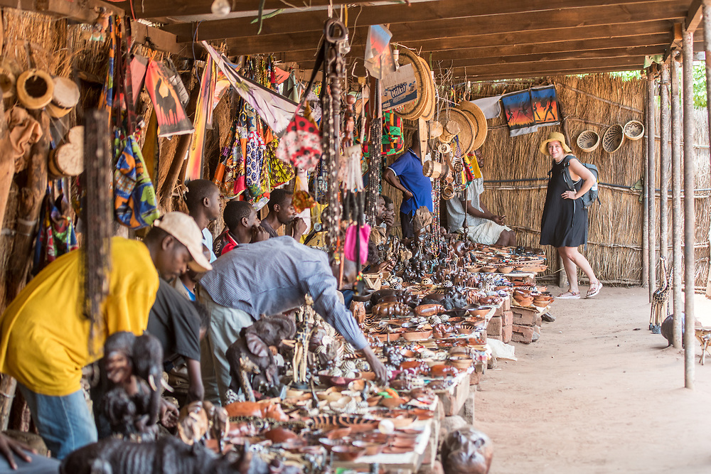 Zambian vendors sit behind table filled with handcrafted souvenirs while young woman tourist browses, Mukuni Village, Zambia