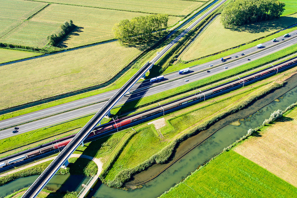 Nederland, Gelderland, Gemeente Neder-Betuwe, 30-09-2015; goederentrein passeert de Betuwelijn (Tiel - Gorinchem) onderweg van Duitsland naar de Haven van Rotterdam op de Betuweroute. Omgeving Ochten, de autosnelweg A15 loopt parallell aan de spoorlijn, evenals rivier de Linge.<br /> Freight train en route from Germany to the Port of Rotterdam on the Betuweroute.  A15 motorway runs parallell to the railroad.<br /> luchtfoto (toeslag op standard tarieven);<br /> aerial photo (additional fee required);<br /> copyright foto/photo Siebe Swart