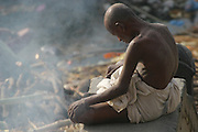 An exhausted mourner sits above the cremation grounds at Manikarnika Ghat and lets ashes rain down on him. One hundred or more times a day male family members carry a loved one's body through the narrow streets on a bamboo litter to the Ganges River shore, a place of pilgrimage for Hindus during life, and at death.