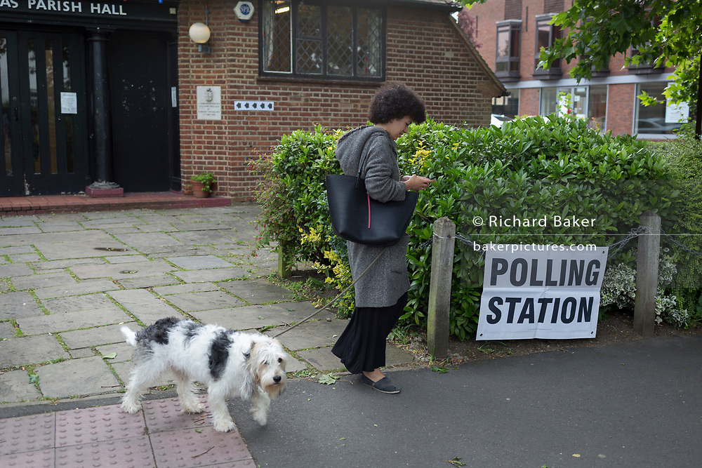 Dog owning voter arrives for the UK 2017 general elections outside the polling station at St. Barnabas Parish Hall in Dulwich Village  on 8th June 2017, in London, England.