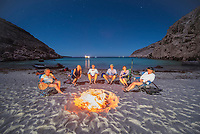 Beach fire after a BBQ on Isla Espiritu Santo on a full moon with stars in Baja California Sur, Mexico.