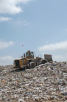Digger working at landfill site