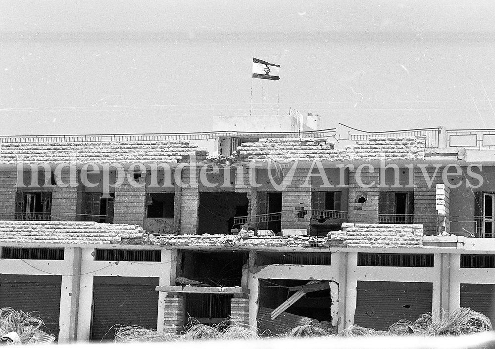 Christian Lebanese Sentry on guard duty near the road block set up after the Israeli withdrawl from South Lebanon, the road leading to the town of Bint Jbeil , Bombed building with the Lebanese Flag 14/06/1978 (Part of the Independent Newspapers Ireland/NLI Collection).