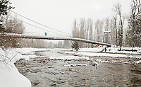 A woman crossing the Tawks-Foster suspension bridge over the Methow river near Mazama, Washington, USA.