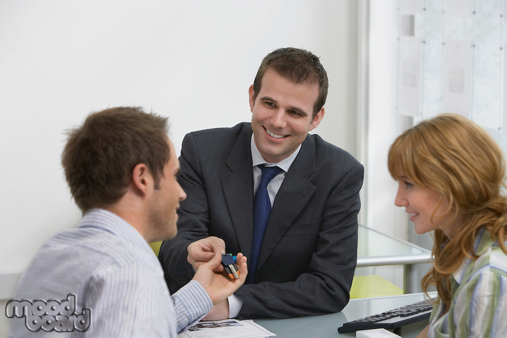 Couple in estate agents real estate agent handing man pens