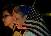 Candlelight bathes the faces of Justine Ryan and friend Nicole Reese, both of Milwaukie, as they attend a vigil at Waterfront Park in Portland for terrorist attack victims Wednesday night. Justine smiles as people begin to talk of world peace and an end to hatred.