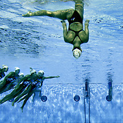 The synchronized swimming team from Japan (foreground left and top) practiced their team entry routines while sharing the pool with teams from other countries at the Olympic Aquatic Centre in Athens, Greece on August 26, 2004.