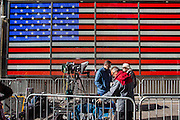 Media people setting up camera equipment in a designated area ring fences with crowd control barriers, in front of a large digital Flag of the United States on the side of the US Armed Forces Recruiting Station in Times Square, Midtown Manhattan, New York City, New York, United States.   (photo by Andrew Aitchison / In pictures via Getty Images)