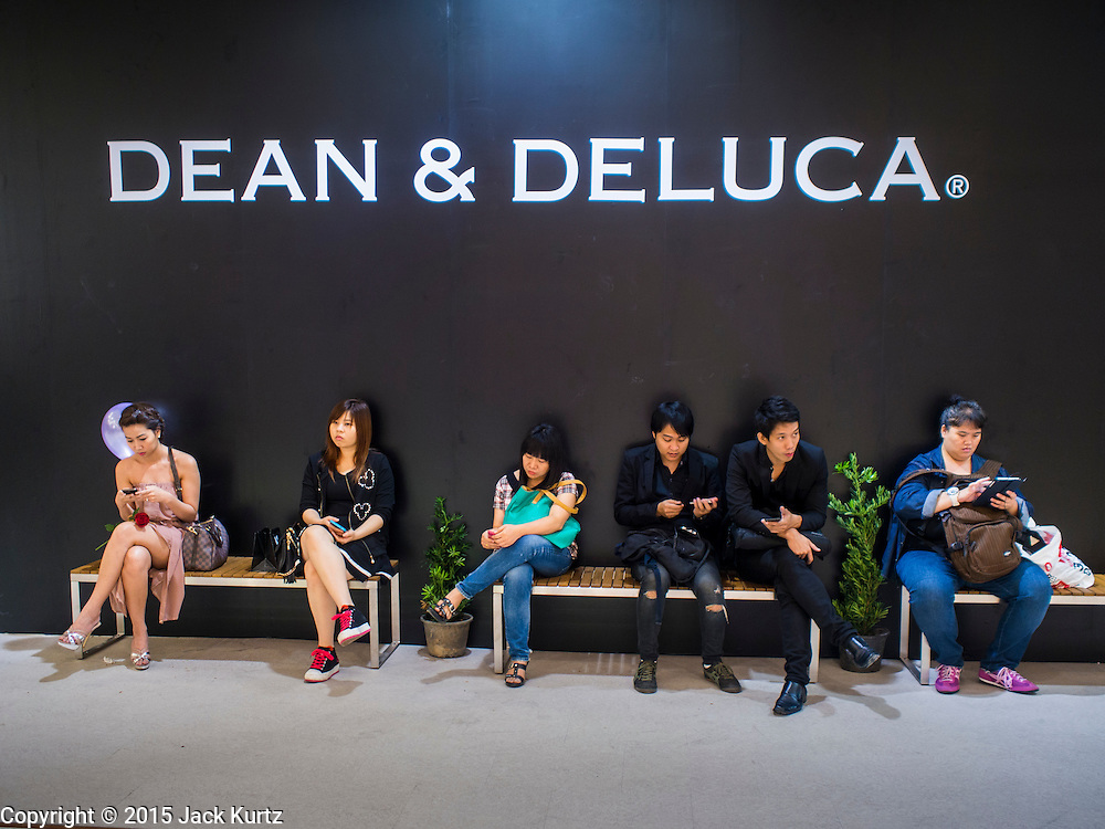 "27 MARCH 2015 - BANGKOK, THAILAND: Shoppers wait in front of what will be a Dean & Deluca store in ""EmQuartier,"" a new shopping mall in Bangkok.  ""EmQuartier"" is across Sukhumvit Rd from Emporium. Both malls have the same corporate owner, The Mall Group, which reportedly spent 20Billion Thai Baht (about $600 million US) on the new mall and renovating the existing Emporium. EmQuartier and Emporium have about 450,000 square meters of retail, several hotels, numerous restaurants, movie theaters and the largest man made waterfall in Southeast Asia. EmQuartier celebrated its grand opening Friday, March 27.   PHOTO BY JACK KURTZ"