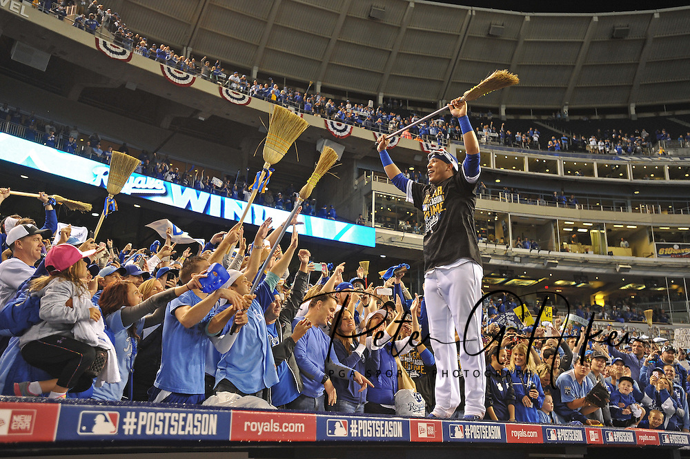 Kansas City Royals catcher Salvador Perez (right) stands on top of the dugout and celebrates with Royals fans after sweeping the Los Angeles Angels and advancing to the ALCS after game three of the 2014 ALDS baseball playoff game at Kauffman Stadium. Mandatory Credit: