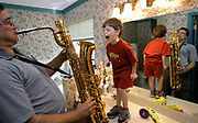 """*PHOTO WAS CHOSEN OUT OF 2,000,000 PICTURES AND PUBLISHED IN THE BOOK """"AMERICA 24/7"""" AND ALSO IN THE UPCOMING """"FLORIDA 24/7""""<br /> <br /> Mike Ewen of Tallahassee, Fla. practices his Tenor Saxophone as his son Nathaniel, 4, tries to match the sound level with his voice. Ewen uses his bathroom to practice because of the good acoustics.(Craig Litten)"""