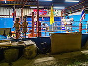 """11 DECEMBER 2014 - THONBURI, BANGKOK, THAILAND:  The Kanisorn boxing gym is a small gym along the Wong Wian Yai - Samut Sakhon train tracks. Young people from the nearby communities come to the gym to learn Thai boxing. Muay Thai (Muai Thai) is a Thai fighting sport that uses stand-up striking along with various clinching techniques. It is sometimes known as """"the art of eight limbs"""" because it is characterized by the combined use of fists, elbows, knees, shins, being associated with a good physical preparation that makes a full-contact fighter very efficient. Muay Thai became widespread internationally in the twentieth century, when practitioners defeated notable practitioners of other martial arts. A professional league is governed by the World Muay Thai Council. Muay Thai is frequently seen as a way out of poverty for young Thais and Muay Thai camps and schools are frequently crowded. Muay Thai professionals and champions are often celebrities in Thailand.    PHOTO BY JACK KURTZ"""