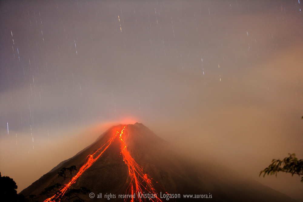 Volcano Arenal, Costa Rica seen at night with clouds around<br /> <br /> The volcano Arenal has been active since 1968 and you can, in fact, still see molten lava flowing down its sides and bursting from its top nearly every day! Its iconic cone and fiery lava make it a photographer's dream, as jaw-dropping images can be captured from every angle and during any time of the day. Activity abounds in the area surrounding the volcano, ensuring that a trip here will never be boring. What's more, the volcano's base is stippled with a handful of thermal hot springs, providing visitors with a sensuous way to relax.<br /> <br /> For more travel photography from Costa Rica visit www.aurora.is<br /> For Travel stories visit www.benzi.is