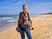 28 OCTOBER 2012 - SAI BURI, NARATHIWAT, THAILAND:   Photojournalist JACK KURTZ on Wasukrit beach in Sai Buri, Thailand. Sai Buri, in Narathiwat province, Thailand, has been the scene of several bloody attacks in Thailand's long running Muslin insurgency. In September, 2012, a large car bomb was detonated in front of a Buddhist owned business in the village killing more than 9. In October, 2012, in a possible revenge attack, hand grenades were rolled into a crowd of Muslim diners, injuring nine. More than 5,000 people have been killed and over 9,000 hurt in more than 11,000 incidents, or about 3.5 a day, in Thailand's three southernmost provinces and four districts of Songkhla since the insurgent violence erupted in January 2004, according to Deep South Watch, an independent research organization that monitors violence in Thailand's deep south region that borders Malaysia.   PHOTO BY JACK KURTZ