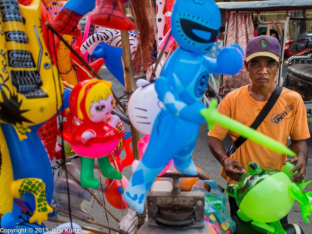 25 FEBRUARY 2015 - PHNOM PENH, CAMBODIA: An inflatable toy vendor near the Royal Palace in Phnom Penh.   PHOTO BY JACK KURTZ