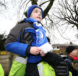 A policeman lifts a young Rochdale supporter as the Tottenham Hotspur team coach arrives
