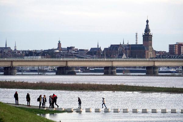 Nederland, The Netherlands, Nijmegen, 28-1-2018Opnieuw is er een golf hoogwater die via de Rijn en Waal ons land passeert op weg naar zee. Het water is iets minder hoog als drie weken geleden, maar mensen nemen weer de gelegenheid ervan te genieten door wandelen langs de Nevengeul, spiegelwaal .   recreatie,wandeling,wandelaars , mensen, ontspannen,ontspanning .Foto: Flip Franssen