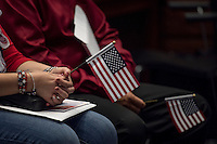 U.S. citizen applicants hold American flags during a naturalization ceremony at the Evo A. DeConcini U.S. Courthouse in Tucson, Arizona, U.S., on Friday, Sept. 16, 2016. Photographer: David Paul Morris/Bloomberg