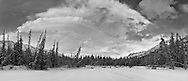 With the frozen Eagle River in the foreground, a weather front moves into Eagle River Valley along the Chugach Mountains of Chugach State Park in Southcentral Alaska. Morning. Winter. Composite panorama.