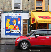 "Austin Mini parked in front of a ""Spice"" coffee shop and a colorful spray paint graffiti building showing a figure of the Front Populaire (Popular Front) in Miro's style and ""Aidez Espana"" written, Notting Hill, London, UK. Picture by Manuel Cohen"