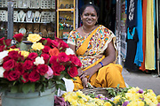 PUTTARPATHI, INDIA - 27th October 2019 - Portrait of cheerful lady selling flowers at a market in Puttarpathi, Andhra Pradesh, South India