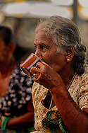 An elderly woman drinking a cup of sri lankese tea in a local market, Negombo, Sri Lanka