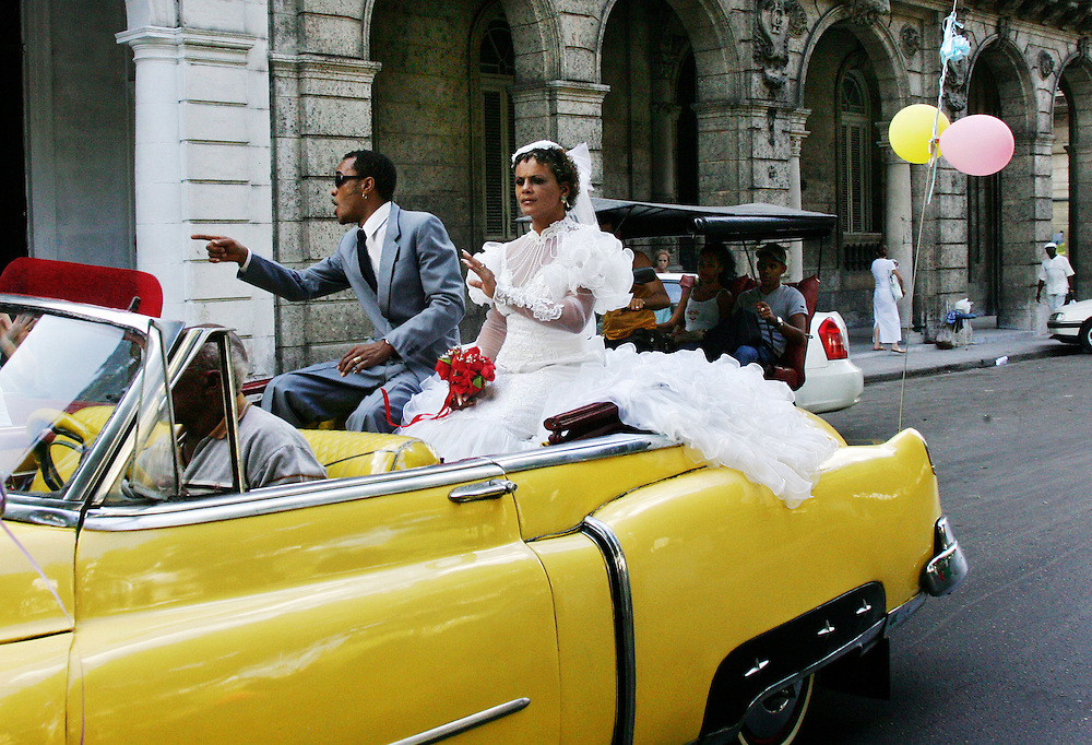 A couple drive through the streets of Old Havana, Cuba after tying the knot.