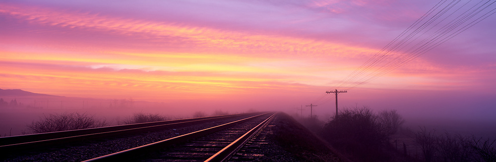 Train tracks with pinks sunrise sky
