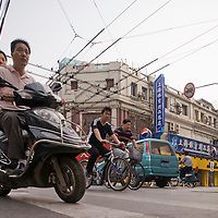 Asia, China, Shanghai, Couple on motor scooters rides in crowded streets along Sichuan Road in the city's Bund District during morning rush hour.