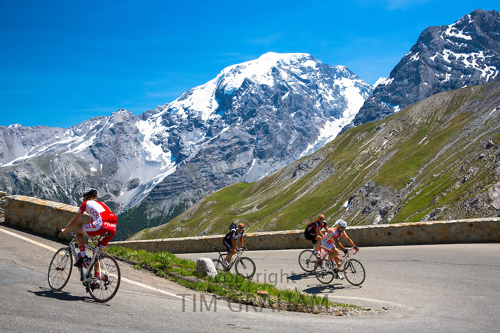 Cyclists ride roadbikes uphill on The Stelvio Pass, Passo dello Stelvio, Stilfser Joch, in the Alps, Italy