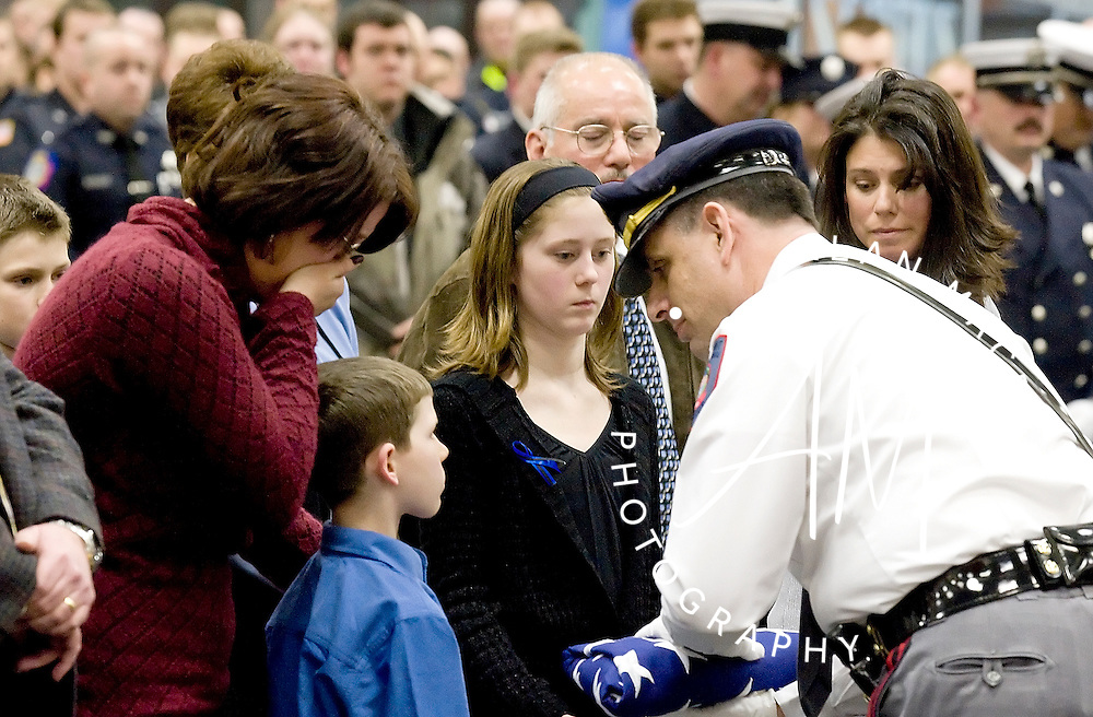 Belmont Police Chief Vincent Baiochetti presents an American flag to Bryan and Kiersten Slater, children of fallen Belmont Police Officer Kier Slater, at the conclusion of a memorial service at the NH Police Academy on Wednesday, February 13, 2008.  To the children's left is their mom, Brena Young of Belmont and on the right is Slater's fiancee, Police Officer Michelle Moir.  (Alan MacRae/for the Citizen)