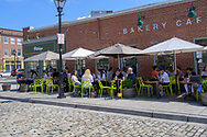 Fells Point, Baltimore, MD, USA -- April 13, 2019. Diners enjoy having coffee and breakfast outside in Fells Point, Baltimore on a spring morning.