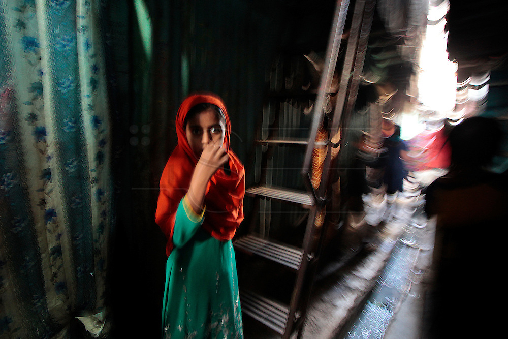 A young girl walks the dark alley ways in the slum.  The slum of Cheetah Camp on the outskirts of Mumbai, India is a predominantly muslim community on living on the fringe while the city continues to grow.